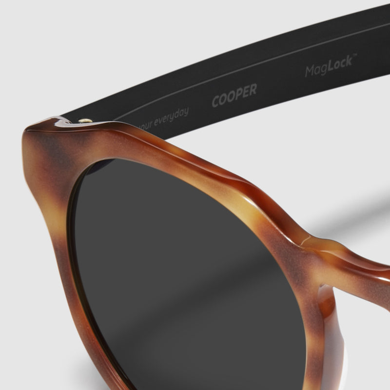 close up view of distil cooper sunglasses with matte tortoise frames and polarized lens