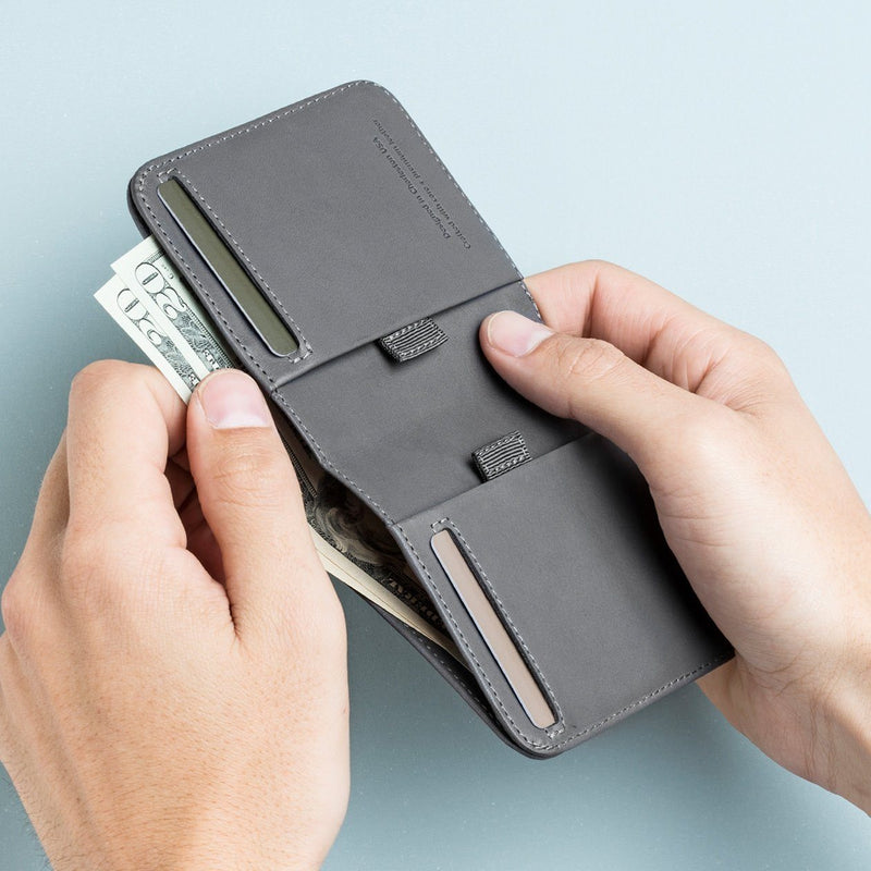 two hands taking bills out of a wally agent slim billfold wallet in gray leather designed by distil