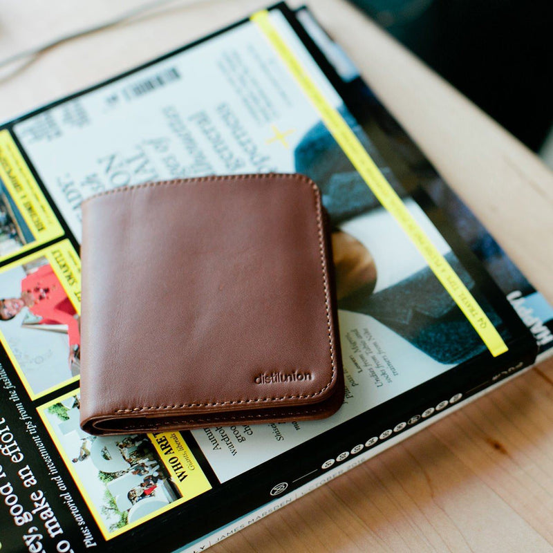 closed distil hickory leather slim billfold wallet on a magazine on a table