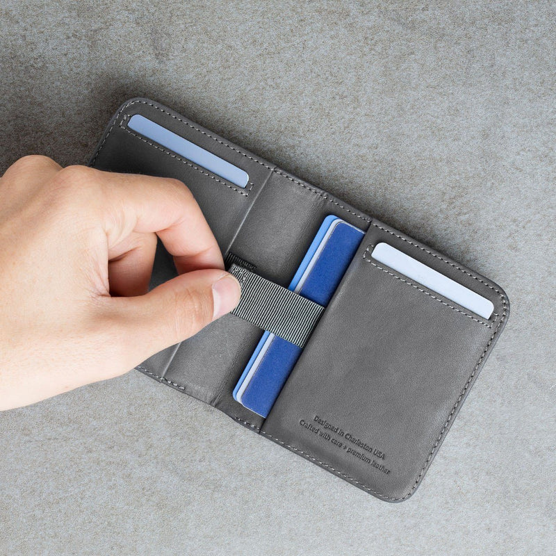left hand using the pull-tab to take out cards from the slate colored slim billfold wallet