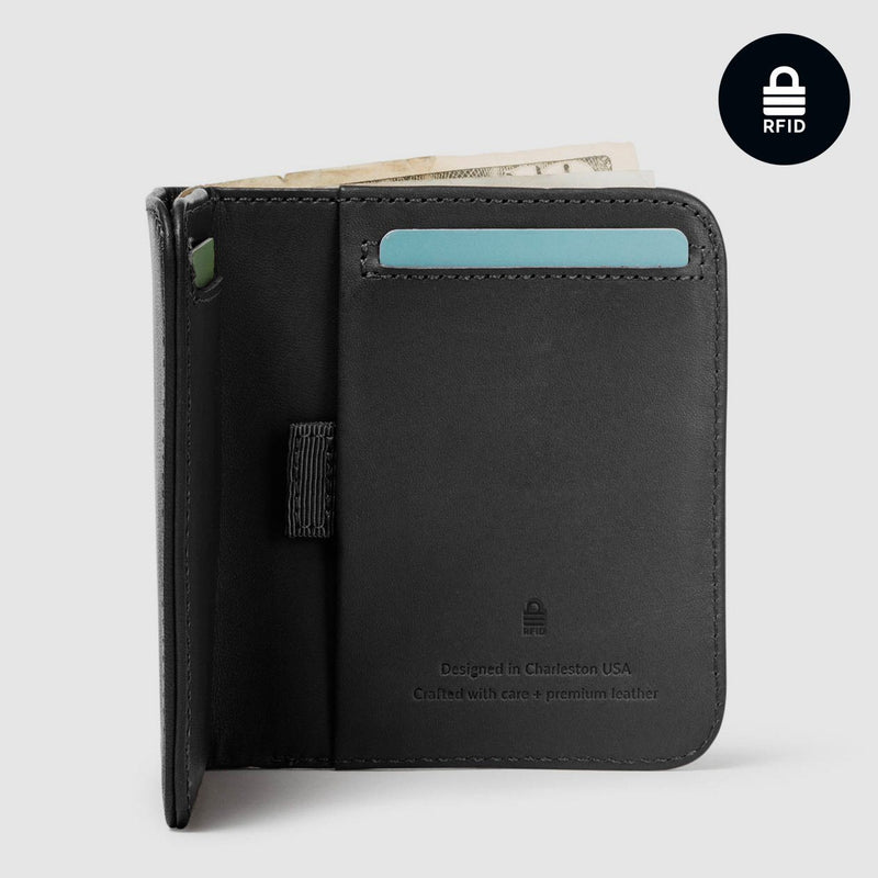 opened distil ink black billfold wallet with rfid protection, a card and paper bill protruding