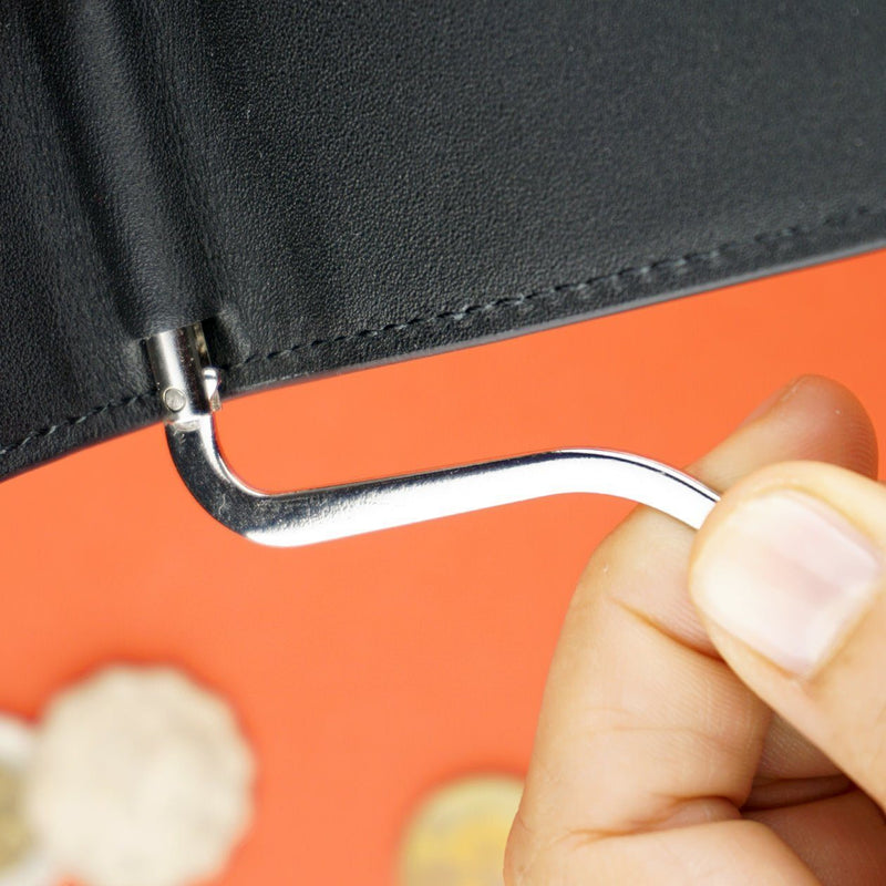 index and thumb holding an adjustable money clip attached to a black wallet