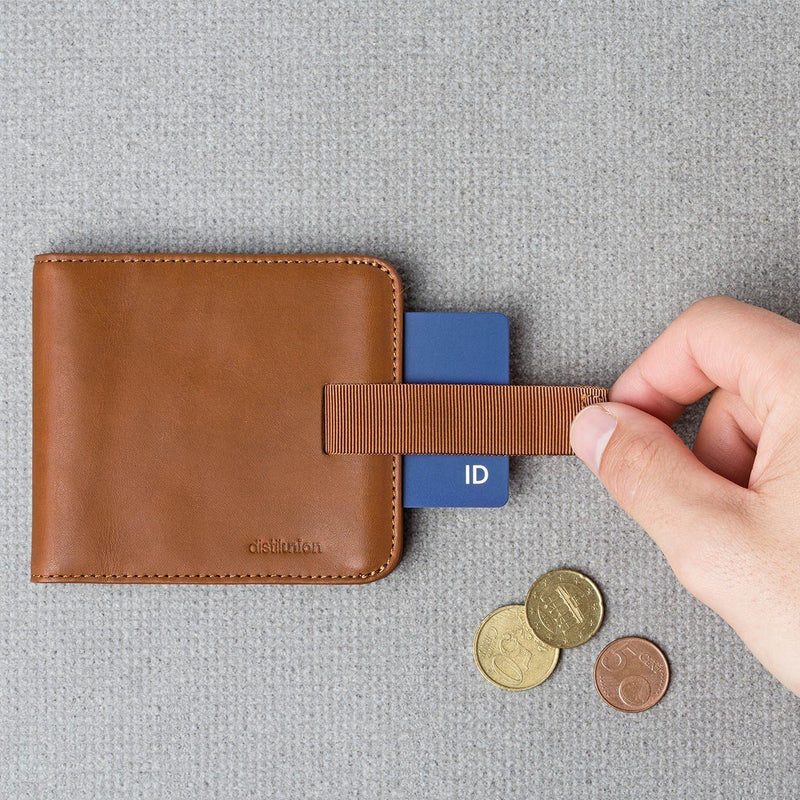 hand using pull-tab to extract brown card from hickory leather wally euro travel wallet