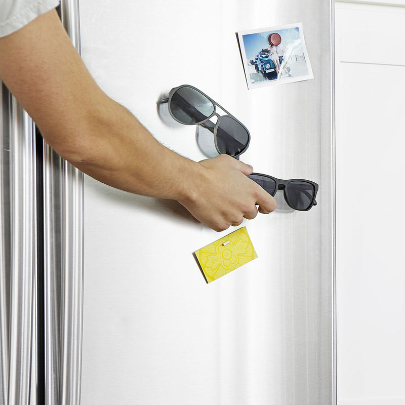 right arm attaching sunglasses onto fridge door with a photograph, aviator sunglasses and a post-it note