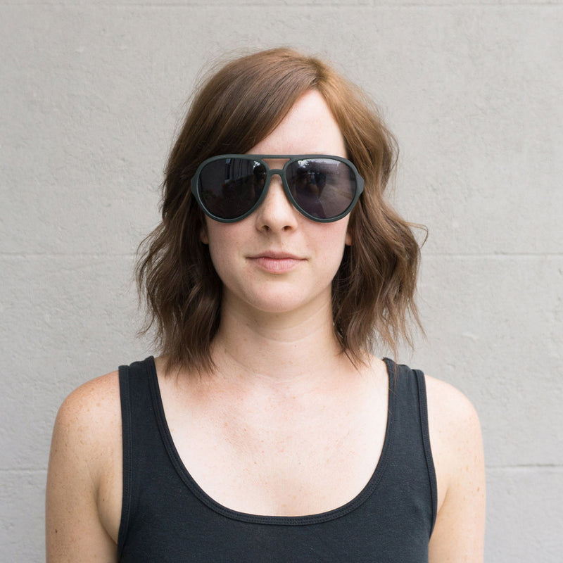 girl with brown shoulder length hair wearing distil sullivan sunglasses and black tank top