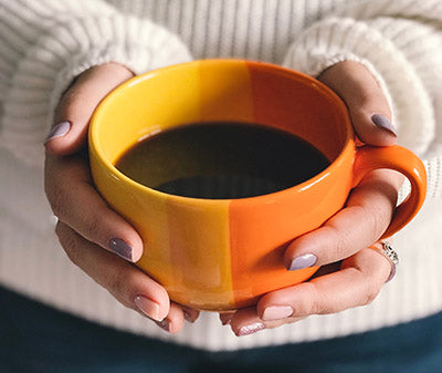 woman chasing chill of changing seasons by warming hands on coffee cup