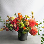 Bright orange, yellow, pink, and lime green summer flowers in blackened metal vase