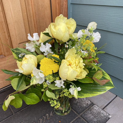 bright yellow flowers and green foliage in clear glass vase