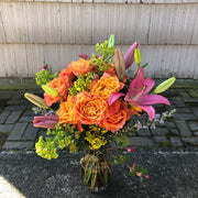 orange roses with pink lilies in a clear glass vase