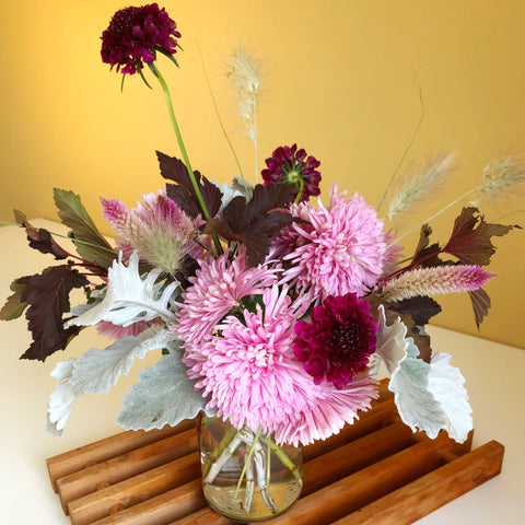 deep and soft purple flowers with fall foliages in glass vase