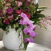 Very large arrangement of purple and pink seasonal and tropical flowers with greenery in white ceramic vase