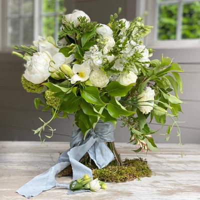 bridal bouquet with white flowers and green foliage and finished with silk ribbon