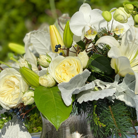 white flowers and winter greens in a urn style centerpiece