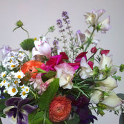 Bright summer mixture of purple, pink, white, peach flowers with greenery in gold tin vase