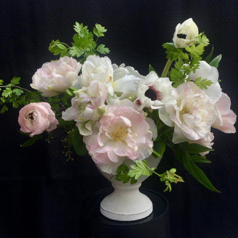 blush tone blooms with spring greens in vessel