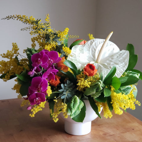 bright yellow, purple, and white tropical flowers in white ceramic vase