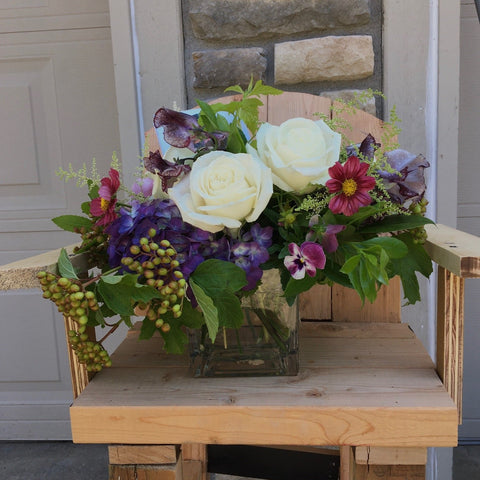 white roses with purple flowers and berries in square vase