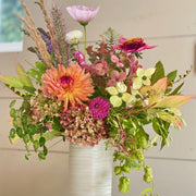fall flowers in orange, pink, and purples with fall greens in tall ceramic vase
