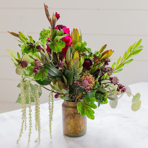 burgundy notes with seasonal greenery in glass vase