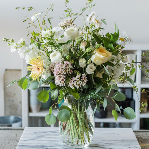 soft whie and pale yellow flowers with mixture of greenery in glass vase