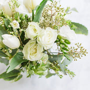 white flowers and greenery in clear glass vase