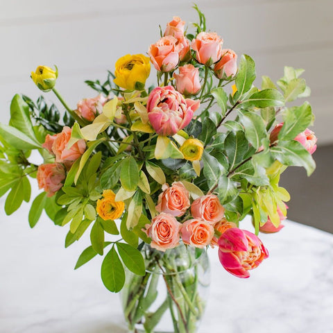 yellow, orange and pink flowers with greenery in clear glass vase