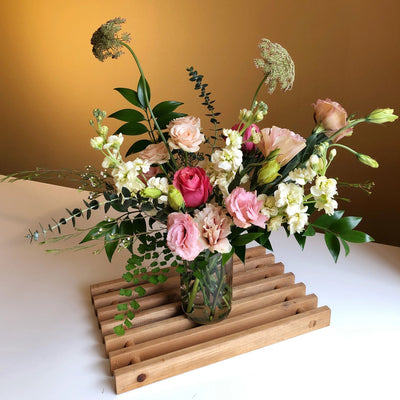 pink and yellow flowers with greenery in clear glass vase