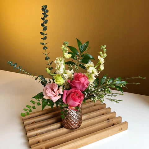 pink and yellow flowers with greenery in blush pink vase