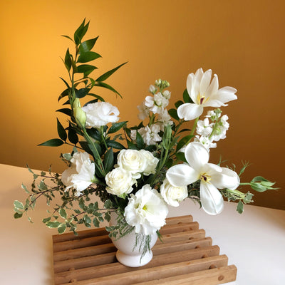 white flowers with greenery in white ceramic vase