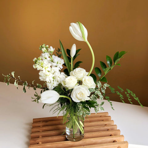 white flowers with greenery in clear glass vase