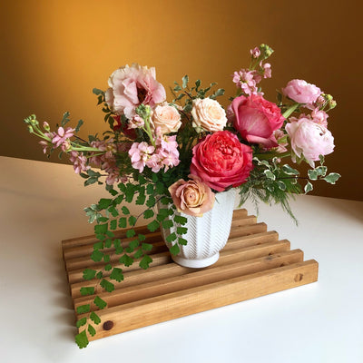 pink flowers with greenery in white ceramic vase