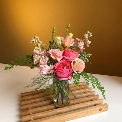 pink flowers with greenery in clear glass vase