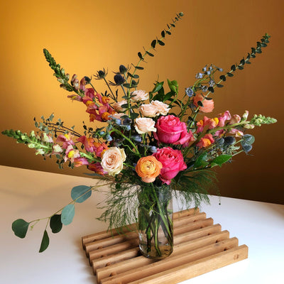 pink, oranges, and blue flowers in clear glass vase