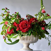red flowers, bright green foliage in brass footed vessel