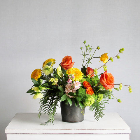 Vibrant yellow, orange, and peach flowers in metal container with spring foliage