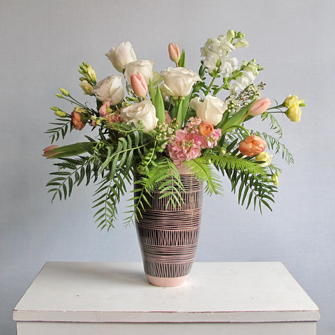 large painted ceramic vase with white roses, and pink flowers with greenery