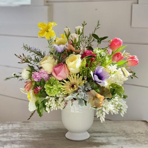 Assortment of bright and soft pink flowers in white ceramic vase