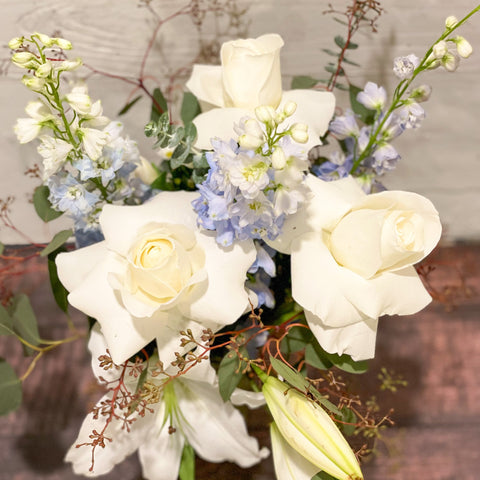 White flowers and soft blue accents and greenery