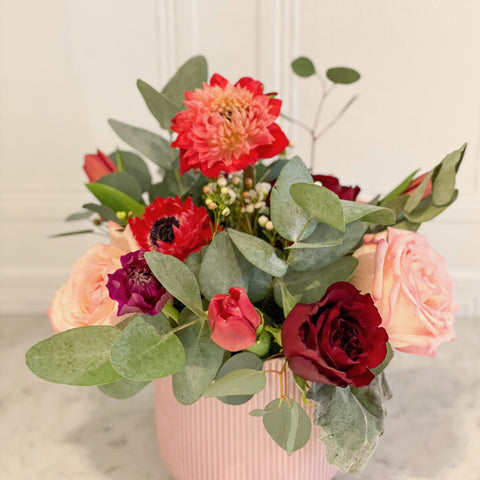 bright cheery flowers with eucalyptus greenery in complimentary vase