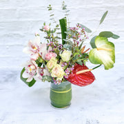 tropical flowers with orchids, anthirium and roses with greenery
