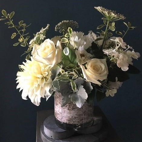 white flowers with greens in cylinder vase