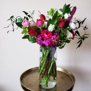 Bright pink, purples, whites and greens fill this clear glass vase