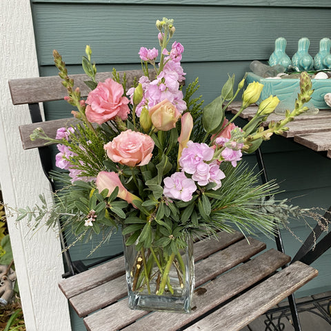 candy pink blooms with winter greens in glass vase