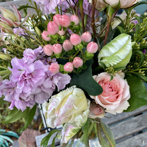 Soft pink and lavendar flowers with greenery in clear glass vase