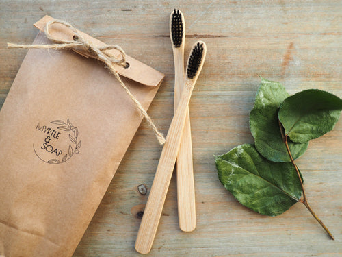 Set of two bamboo toothbrushes with their eco friendly packaging.