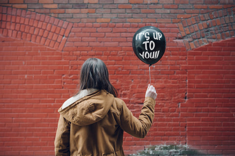 "Someone stands and is clearly inspired as they hold a balloon with motivational writing on it.""Up To You"""