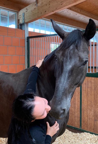 Hope next to a dark bay horse, Destar, kissing him on the nuzzle.