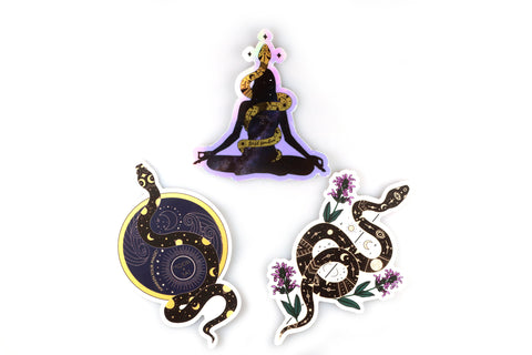 "Galaxy silhouette of a woman meditating in easy pose with golden serpent covered in black celestial accents wrapped around her body. This sticker says ""wild wonderer"" and ""moon and jai."" The Awaken your magic sticker with a serpent passing through a circle and Cosmic Serpent sticker with purple flowers sticking out of a black boho serpent are also included in this pack.  Edit alt text"