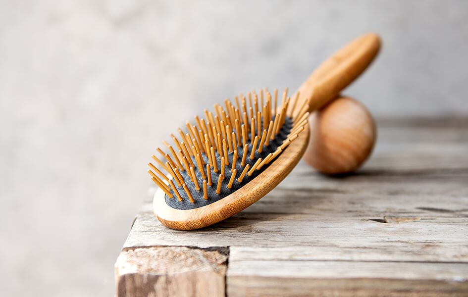 A classic-looking wooden hairbrush balanced on a wooden ball, which are both lay on a rustic table