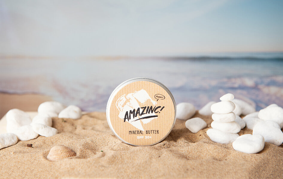 A plastic-free aluminium tin of sun cream on sand surrounded by white pebbles